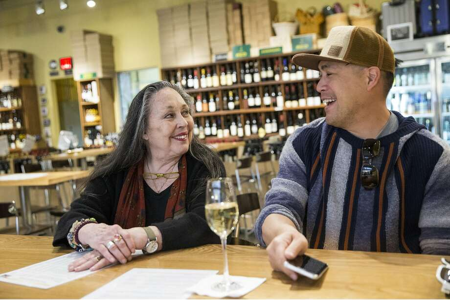 Jeanne Rose has a glass of champagne at Ferry Plaza Wine Merchant with her friend Jeff Chan (right) after shopping at the Ferry Plaza Farmers Market. Photo: Laura Morton, Special To The Chronicle