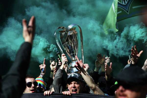 The Emerald City Supporters carry the MLS Cup to the stadium during the march to match prior to the Sounders season opener against New York, Sunday, March 19, 2017 at CenturyLink Field. (Genna Martin, seattlepi.com)