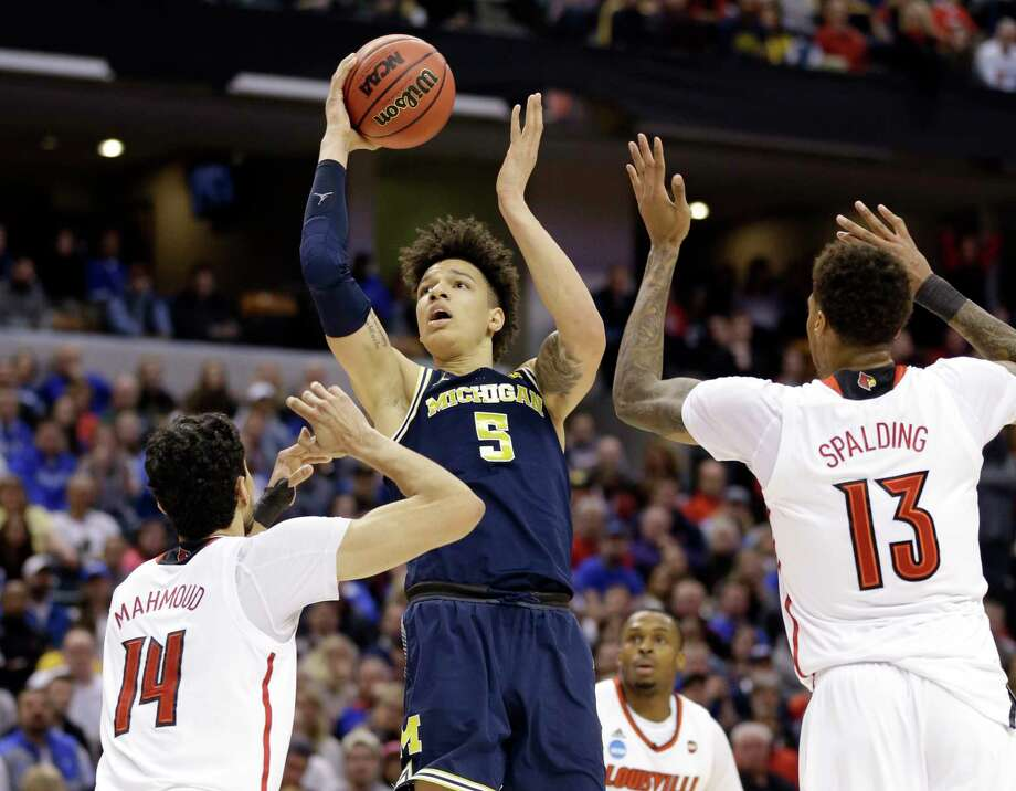 Michigan forward D.J. Wilson (5) shoots over Louisville forward Anas Mahmoud (14) and forward Ray Spalding (13) during the second half of a second-round game in the men's NCAA college basketball tournament in Indianapolis, Sunday, March 19, 2017. Michigan defeated Louisville 73-69. (AP Photo/Michael Conroy) ORG XMIT: INMC122 Photo: Michael Conroy / AP