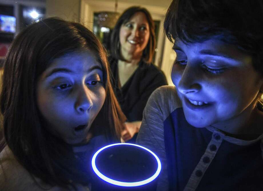 Children mess around with the family's Alexa, an Amazon Echo voice assistant, while their mom watches in Bethesda, Md. The original Echo model was discounted 50 percent, to $89.99. The smaller Echo Dot, at 30 percent off, and the Kindle Fire 7 tablet with Alexa were also among the top deals during Amazon Prime Day on Tuesday. Photo: Bill O'Leary /Washington Post / The Washington Post