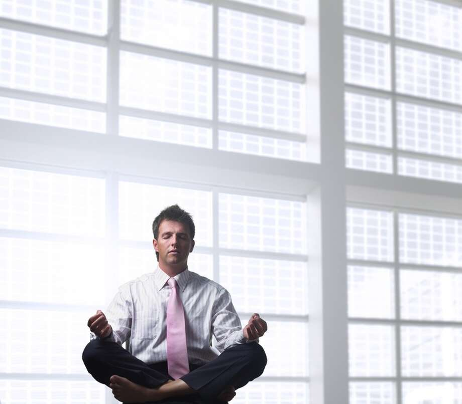 Handsome businessman is relaxing in the office, sitting in a traditional yoga lotus position. meditation  FOTOLIA Photo: Zsolt Nyulaszi, Photographer / handout / stock agency
