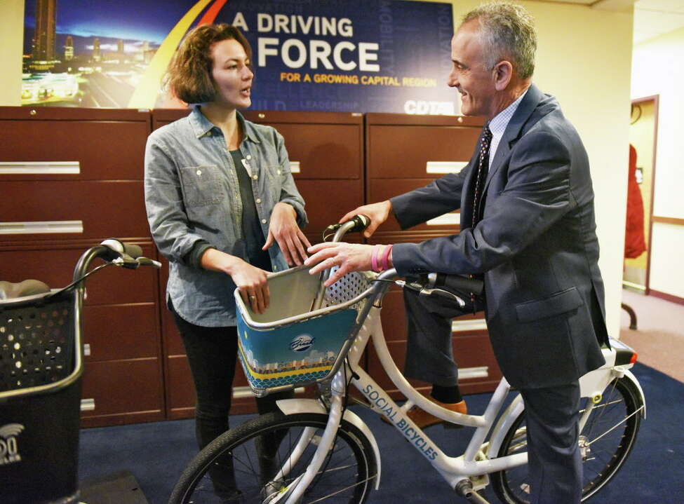 Joanna Jacob of Social Bicycle and CDTA CEO Carm Basile unveil details of CDTA's upcoming bike share program during a news conference Wednesday Dec. 14, 2016 in Albany, NY. The new program will begin this summer, (John Carl D'Annibale / Times Union)