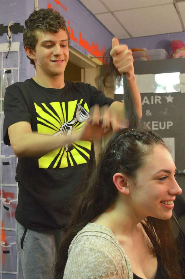"""Sophia Sherman, 16, has her hair done by Antonio Antonelli, 15, in preparation for the Staples High School Players' performance of """"Urinetown, the Musical,"""" Friday, March 17, 2017, in Westport, Conn. The Staples High School Players' spring production of """"Urinetown, the Musical"""" got under way last weekend, and continues this Friday. Cast and crew assembled early in the afternoon to prepare for the show — donning wigs, applying makeup, and making last-minute adjustments to the set. The 2001 musical, which parodies other musicals and a range of social institutions, runs Friday and Saturday, March 24 and 25. For more information visit www.staplesplayers.com. Photo: Jarret Liotta / For Hearst Connecticut Media / Westport News Freelance"""