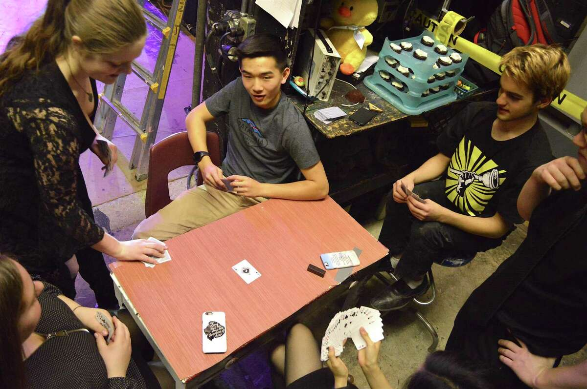 Members of the tech crew pass some time with a little cards before the Staples High School Players' performance of