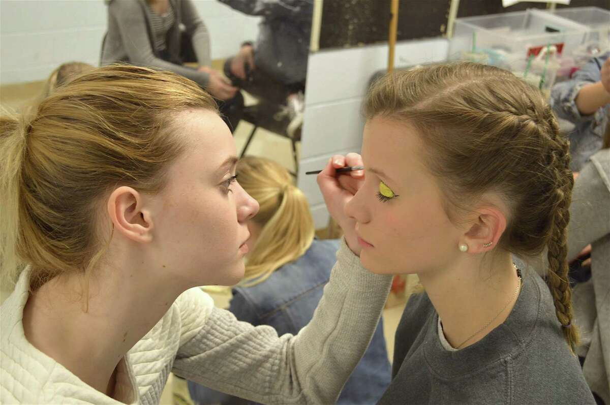 Courtney Hoile, 15, applies makeup to Jill Gault, 17, before the Staples High School Players' performance of