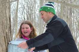 Ben Tsocanos of Darien and daughter Marianne, 9, check their sap bucket at the New Canaan Nature Center's Syrup Saturday: Pancake and PJ's Brunch, Saturday, Mar. 18, 2017, in New Canaan, Conn.