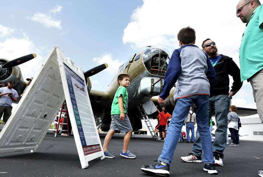 Eli Balderas, 6, left to right, his cousin Nathan Balderas, 10, Jim Balderas, and Jaime Balderas looks at the information on the B 17 G Flying Fortress at the Wings of Freedom Tour on display at Stinson Municipal Airport on Friday, March 17, 2017.  The display, which is open to visits and flights, will go on thru Sunday, March 19th. Photo: Bob Owen, Staff / San Antonio Express-News / ©2017 San Antonio Express-News