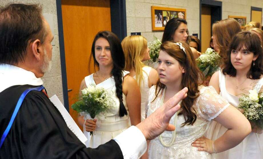 Hillary Donahue, left, and Jessie Price, center, receive instructions from Dean J.P. Mander before leading the procession during graduation exercises at Canterbury School in New Milford on Tuesday, June 1, 2010. Photo: Michael Duffy / The News-Times
