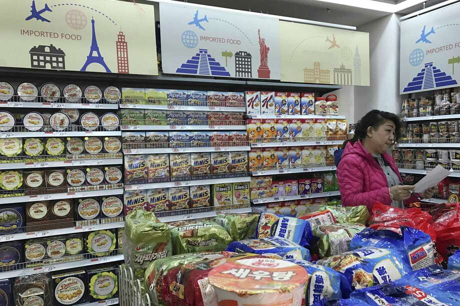 A vendor takes stock of imported food at a mall in Beijing, China. China plans to require intensive inspections of food imports — including such low-risk items as wine and chocolate. China's trading partners say the move could disrupt billions of dollars in commerce. Photo: Ng Han Guan /Associated Press / Copyright 2017 The Associated Press. All rights reserved.