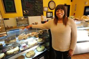 Sandra Williams stands in front of a case of her many cheesecake varieties at La Signature Cheesecakes in the Arcade Mall at 1001 Main Street in downtown Bridgeport, Conn. on Thursday, March 16, 2017.
