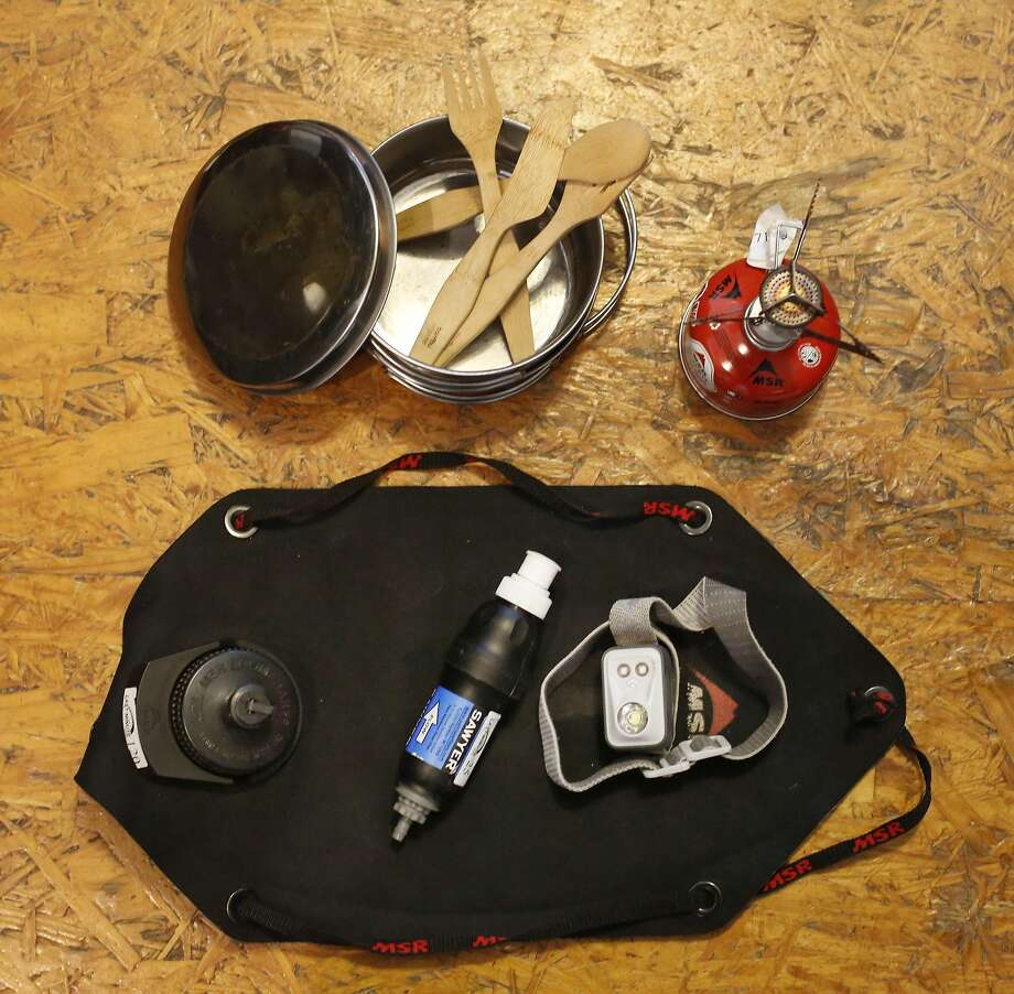 Camping essentials for rent such as pots and pans (clockwise from upper left), utensils, camping stove, headlight, water filtration system and water bag are arranged at Last Minute Gear. Photo: Lea Suzuki, The Chronicle