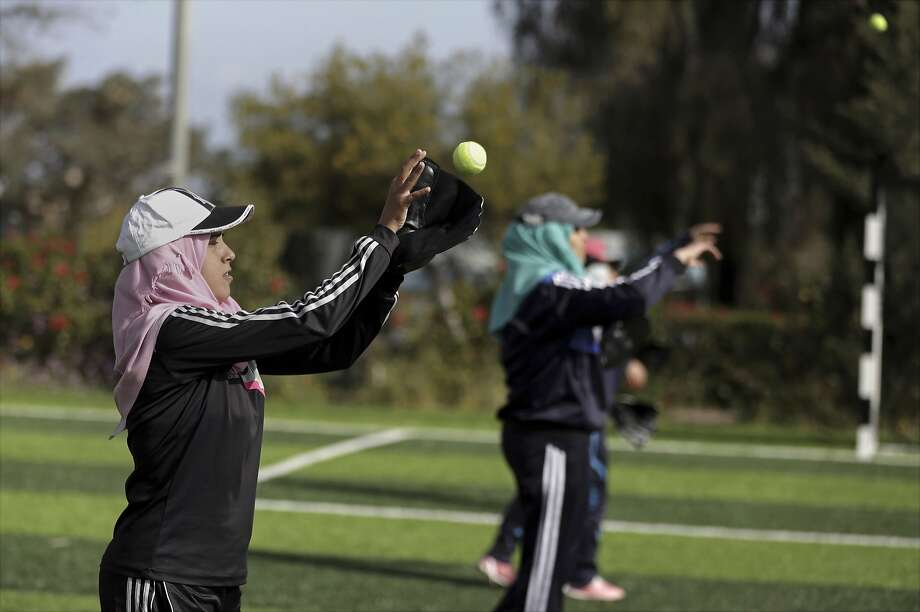In this Sunday, March 19, 2017 photo, Palestinian women practice with tennis balls while training for an all women's baseball game, on a soccer field in Khan Younis, southern Gaza Strip. The female players wear hijabs, not helmets, toss around tennis balls, not baseballs and their leather gloves have been replaced by black imitations knitted from fabric. The group of young women are trying to bring baseball to Gaza -- giving the traditional American pastime a distinctly local feel. (AP Photo/Khalil Hamra) Photo: Khalil Hamra, Associated Press