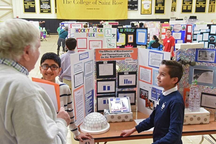 Jay Higle, a science fair judge from Melrose, left, listens as Albany Academy for Boys seventh graders Abrar Zaki, 12, center, and Peter Biegun, 12, right, explain their science project during the 2016 Joseph Henry Science Fair held at College of Saint Rose on Friday, March 17, 2017 in Albany, N.Y. The boys were explaining the effects of wire diameter and thermal conductivity on the regulation of ice. Higle was quite impressed how smart the students were.( Lori Van Buren / Times Union) Photo: Lori Van Buren / 20039924A