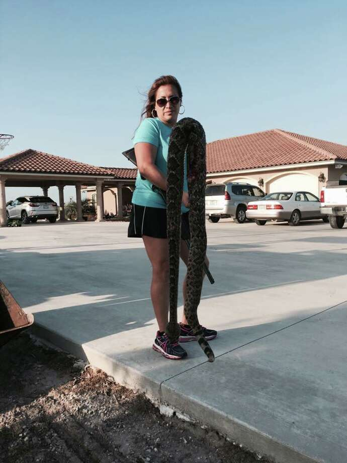 Janie Moy, marine coordinator at Valero Energy, stands with a rattlesnake found in her backyard March 18, 2017.  Photo: Courtesy/Janie Moy