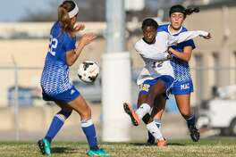 Clemens' Destiny Davis (center) takes a shot at the goal between MacArthur's Alyssa Miller (right) and Jerelyn Valdez during a game in the 2017 North East tournament at Blossom East on Jan. 20, 2017.