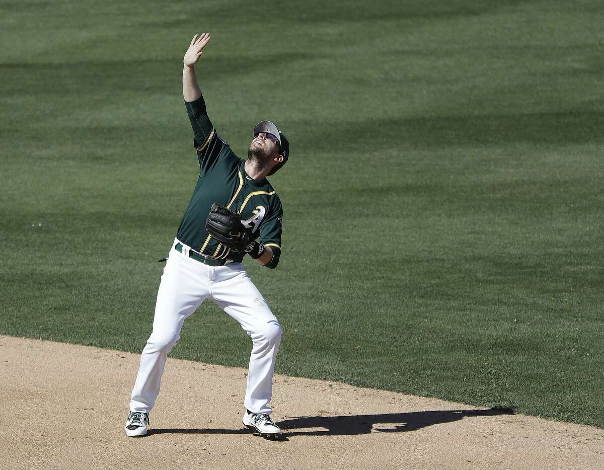 Oakland Athletics' Jed Lowrie shields his eyes during the fourth inning of a spring training baseball game against the Cincinnati Reds, Thursday, March 9, 2017, in Mesa, Ariz. (AP Photo/Darron Cummings)