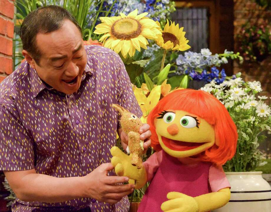 "Alan Muraoka and Julia, a new Muppet character who has autism, play together on ""Sesame Street."" Julia makes her debut April 10. Photo: Zach Hyman, HONS / Sesame Workshop"