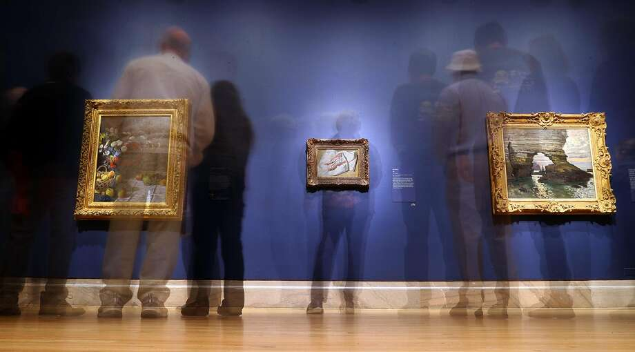 In a 30 second time exposure, visitors view paintings as Fine Arts Museums of San Francisco present Monet: The Early Years at Legion of Honor in San Francisco, Calif., on Sunday, March 19, 2017. Photo: Scott Strazzante, The Chronicle