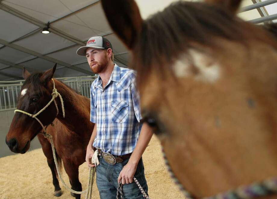 Cody Snow, 20, talks on his way to wash his horses, during down time at Rodeo Village, Wednesday, March 8, 2017, in Houston. ( Jon Shapley / Houston Chronicle ) Photo: Jon Shapley, Staff / © 2017  Houston Chronicle