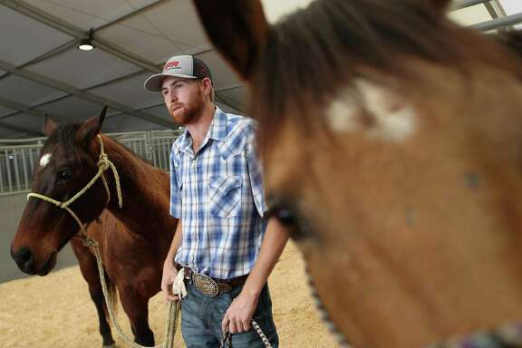 Cody Snow, 20, talks on his way to wash his horses, during down time at Rodeo Village, Wednesday, March 8, 2017, in Houston. ( Jon Shapley / Houston Chronicle )
