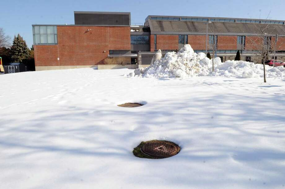 Two man-hole covers can be seen on the playing field at Hamilton Avenue School in the Chickahominy section of Greenwich on Feb. 14. Sylvester Pecora of Chickahominy says that the man-hole covers are part of an underground well system at the school. Pecora says the man-hole covers are unsafe for children playing on the field and Pecora also says that there is a 6-foot incline that runs from the lower end to the upper end of the field that make it unsafe for children at play and causes water to pool towards the lower end of the field and the basketball court. Photo: Bob Luckey Jr. / Hearst Connecticut Media / Greenwich Time