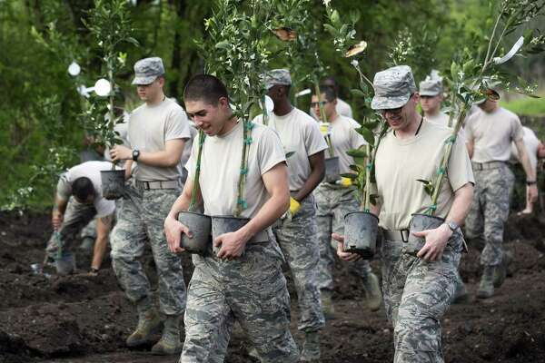 Jacob Elizondo, left, and Reuben Jarrell, right, were among the 200 recent Air Force basic training graduates who planted orange trees while working with the San Antonio Food Bank near Mission San Juan in San Antonio March 18.