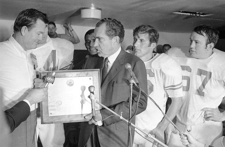 In this Dec. 6, 1969, file photo, President Richard Nixon presents a plaque to Texas football coach Darrell Royal, proclaiming the Longhorns the No. 1 college football team in college football's 100th year, after their 15-14 win over Arkansas in Fayetteville, Ark.