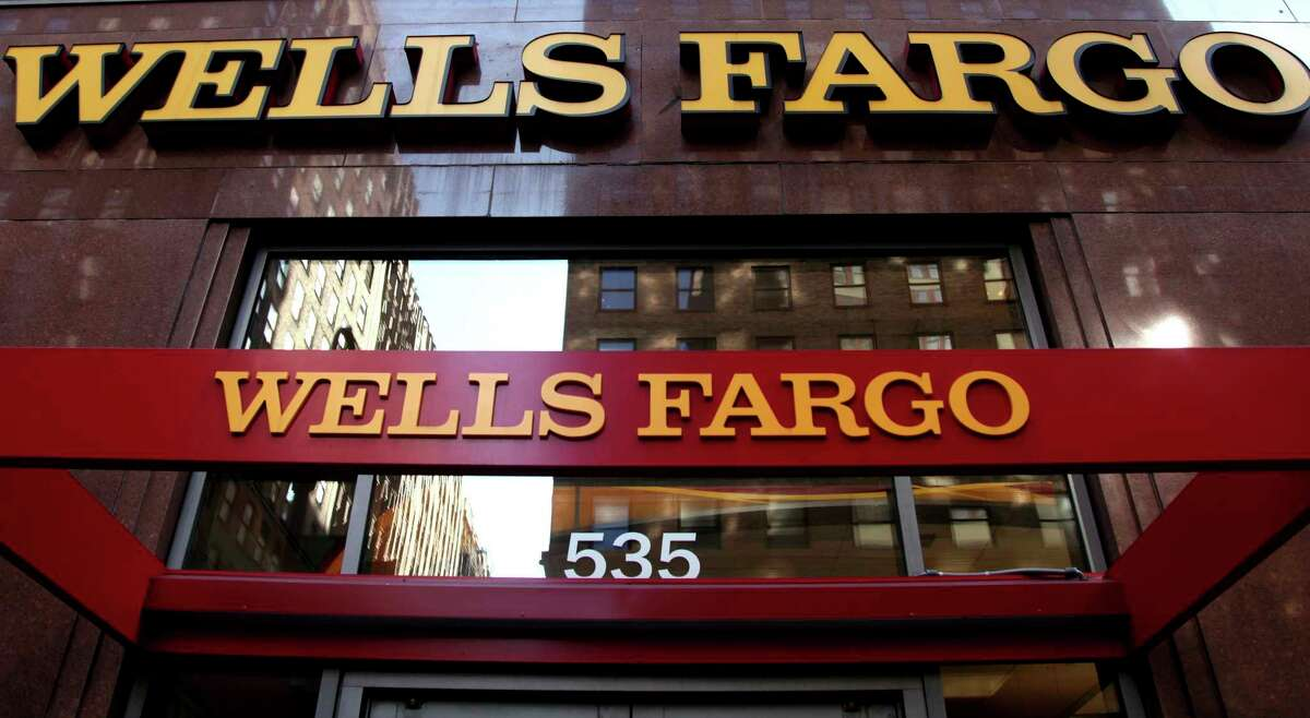 FILE - In this May 6, 2012, file photo, a Wells Fargo sign is displayed at a branch in New York. Wells Fargo's board of directors slashed the bonuses and other compensation of its CEO and seven other top executives on Wednesday, March 1, 2017, a little more than a week after the board publicly fired four senior managers amid an investigation into the bank's sales practices. (AP Photo/CX Matiash, File) ORG XMIT: NYBZ341