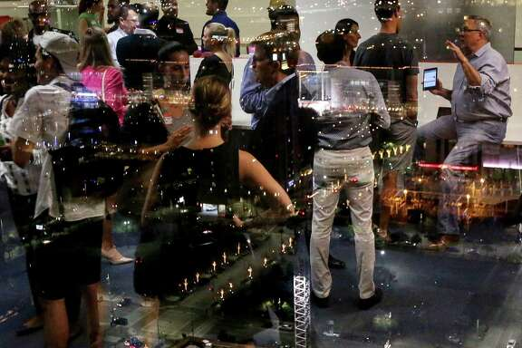 Guests are reflected in a window overlooking Houston during a one-year anniversary party at Station Houston, Wednesday, March 1, 2017, in Houston.