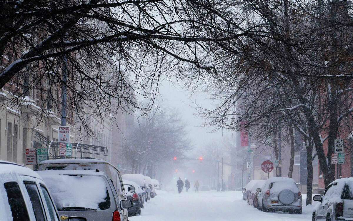 People forgo the snow covered sidewalks and walk in the streets on Tuesday, March 14, 2017, in Troy, N.Y. (Paul Buckowski / Times Union)
