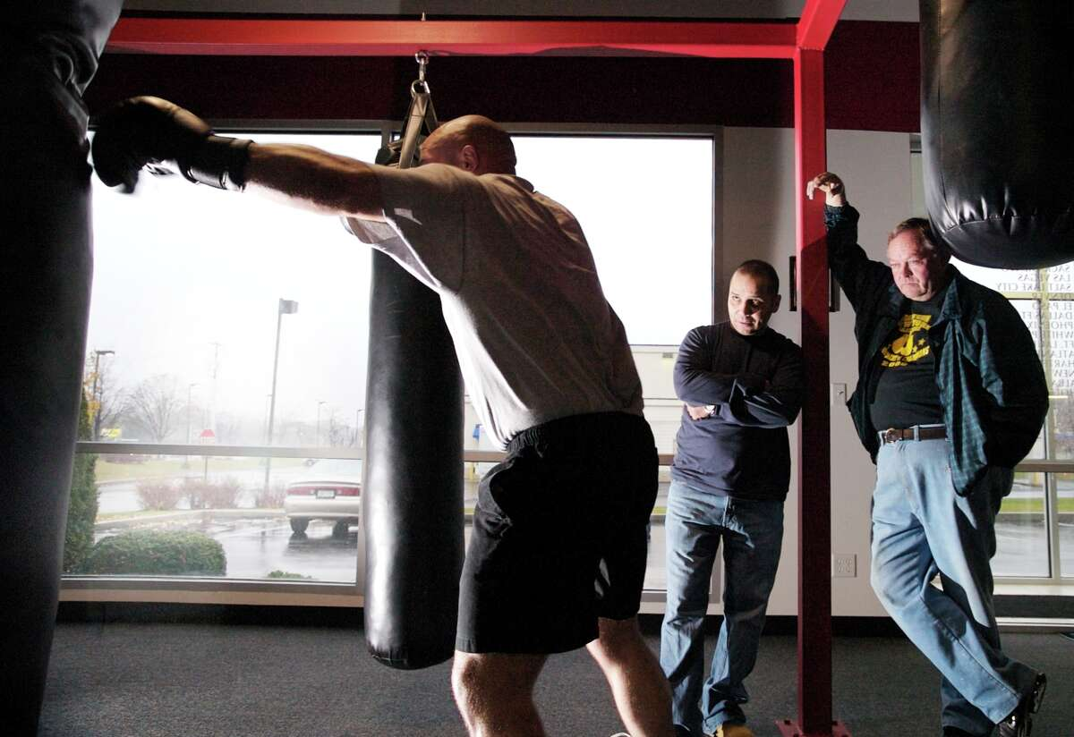 Shannon Miller, left, works on the heavy bag at L.A. Boxing, while corner-men, Bill Growick, middle, and Bob Miller, right, look on, November 8, in Loudonville, NY. (Jon Winslow / SPECIAL TO THE TIMES UNION)