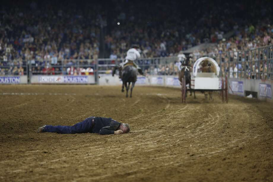 A chuckwagon racer lies in the dirt after he was thrown from his wagon during the Houston Livestock Show and Rodeo Monday, March 20, 2017 in Houston. Medical personnel took him out of the arena on a backboard. ( Michael Ciaglo / Houston Chronicle ) Photo: Michael Ciaglo/Houston Chronicle