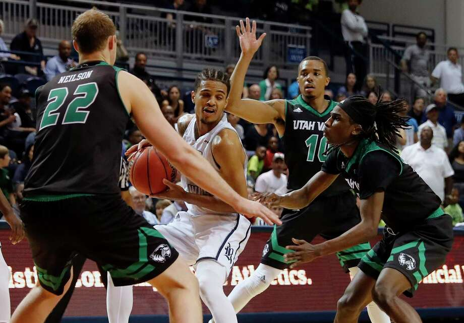Rice Owls guard Marcus Evans (2) controls the ball defended by Utah Valley Wolverines guard Ivory Young (13), forward Isaac Neilson (22), and guard Jordan Poydras (10) in the second half during the College Basketball Invitational second round game between the Utah Valley Wolverines and the Rice Owls at Tudor Field House in Houston, TX on Monday, March 20, 2017.  The Wolverines defeated the Owls 85-79. Photo: Tim Warner, For The Chronicle / Houston Chronicle