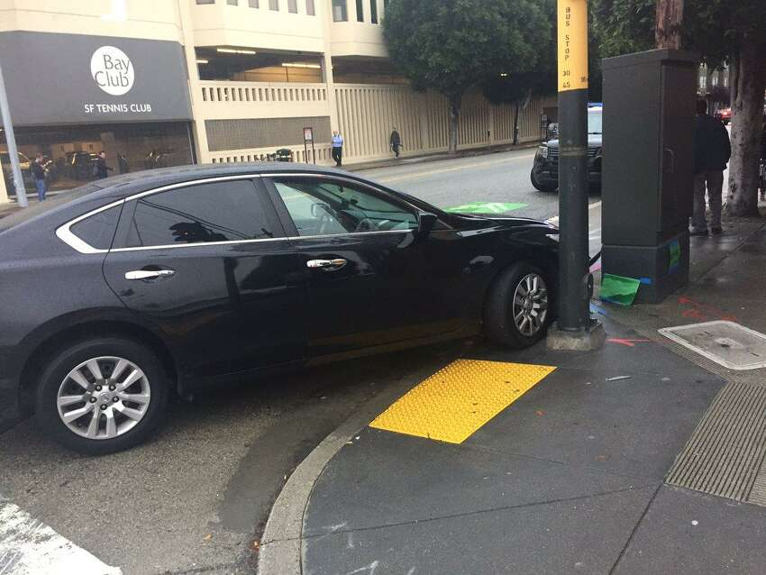 A black Nissan sedan collided with a police car in San Francisco's South of Market neighborhood Monday, injuring the occupants of both cars, police said.