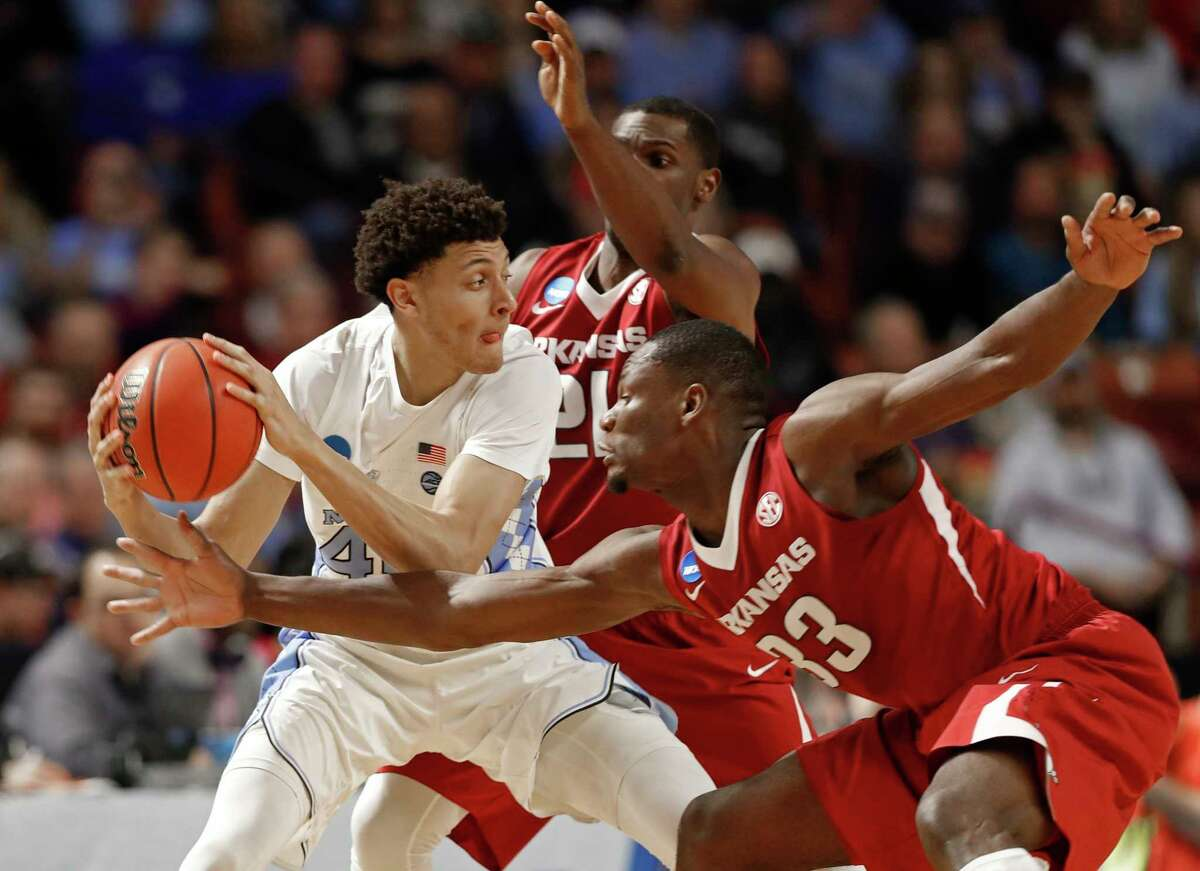 North Carolina's Justin Jackson, left, is trapped by Arkansas' Moses Kingsley, right, and Manuale Watkins, back, during the first half in a second-round game of the NCAA men's college basketball tournament in Greenville, S.C., Sunday, March 19, 2017. (AP Photo/Chuck Burton) ORG XMIT: SCCB119