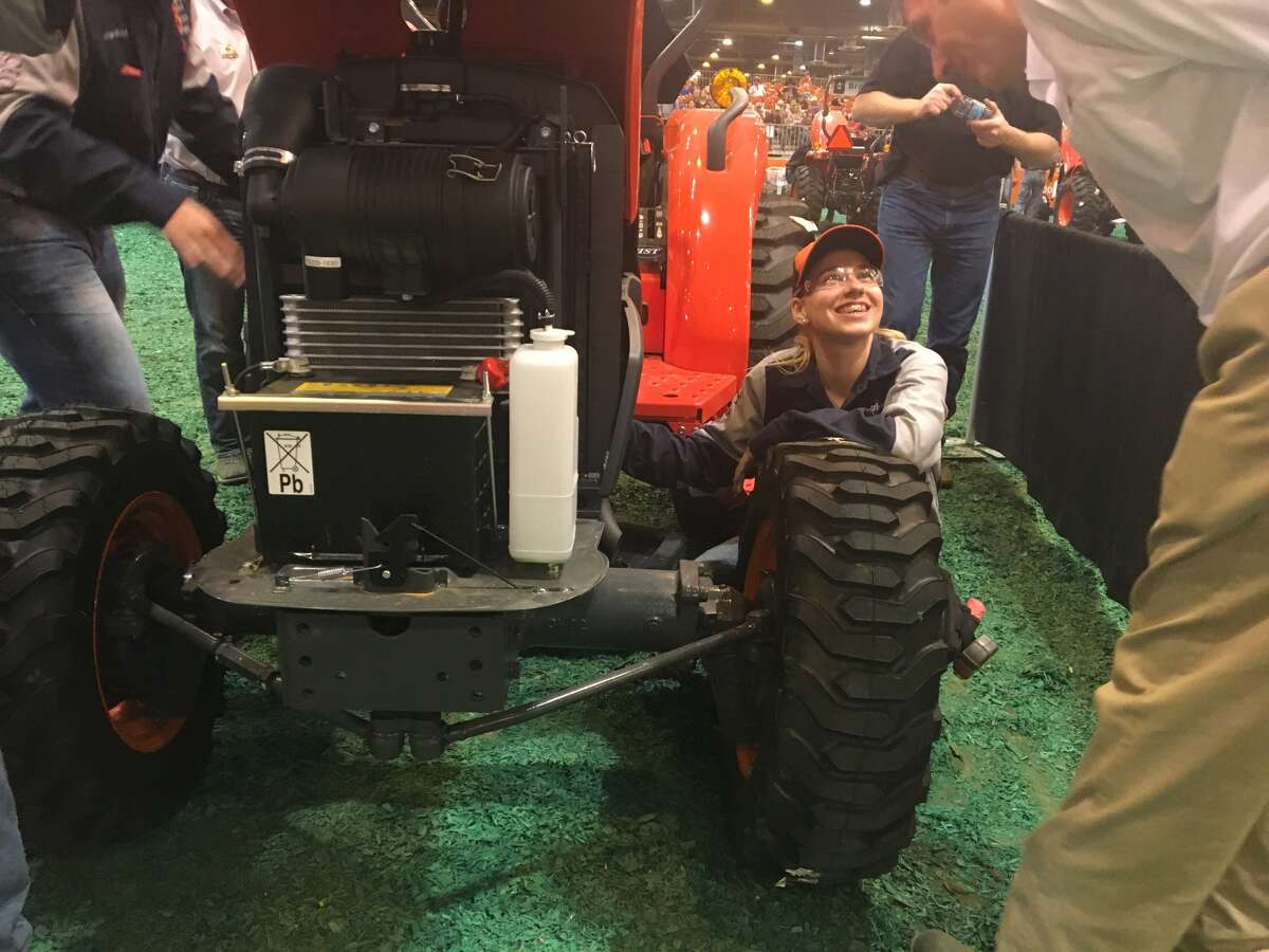 Sage Boettcher, of San Antonio, smiles up at a judge during the FFA Tractor Technician Contest.