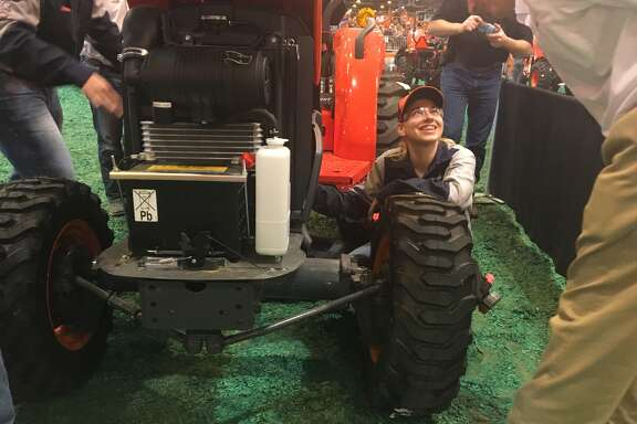Sage Boettcher, of San Antonio, smiles up at a judge during the FFA Tractor Technician Contest at the 2017 Houston Rodeo.