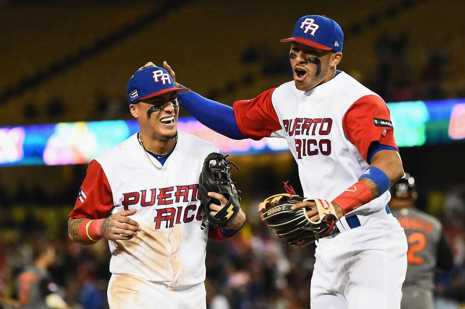 Carlos Correa, left, and T.J. Rivera react after completing a double play to end the 9th inning on Monday. Puerto Rico went on to win 4-3 in 11 innings and advance to the championship game. Photo: Jayne Kamin-Oncea, Getty Images