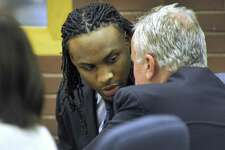 Garfield Sanderson consults with his attorney Michael Courtney during the first day of testimony in his murder trial at Superior Court in Danbury, Tuesday, March 7, 2017.