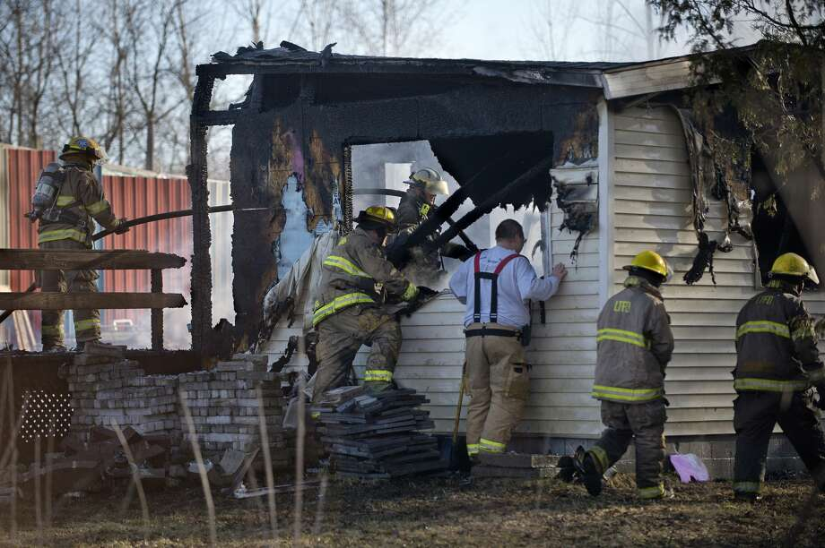 BRITTNEY LOHMILLER | blohmiller@mdn.net Firefighters work to put out a fire at 268 N. 8 Mile Road in Lee Township Tuesday morning. Homer, Lee and Midland Township fire departments responded along Midland County Special Response Unit, MidMichigan Medical Center EMS and Consumers Energy. The flames were knocked down by 9:30 a.m., and firefighters worked to extinguish hot spots. The home was destroyed. Photo: Brittney Lohmiller/Midland Daily News/Brittney Lohmiller