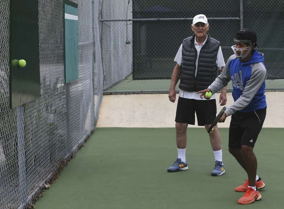 Tennis instructor Ed Hosking, 86, (left) works with tennis player Santiago Padilla (right) on March 20, 2017 at Shadow Cliff Swim and Tennis Club. Hosking employs some unique teaching methods during his days as a coach such as hittiting a tennis ball with the side of the racket. Photo: John Davenport /San Antonio Express-News / ©San Antonio Express-News/John Davenport