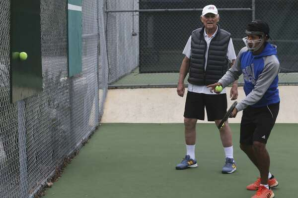 Tennis instructor Ed Hosking, 86, (left) works with tennis player Santiago Padilla (right) on March 20, 2017 at Shadow Cliff Swim and Tennis Club. Hosking employs some unique teaching methods during his days as a coach such as hittiting a tennis ball with the side of the racket.