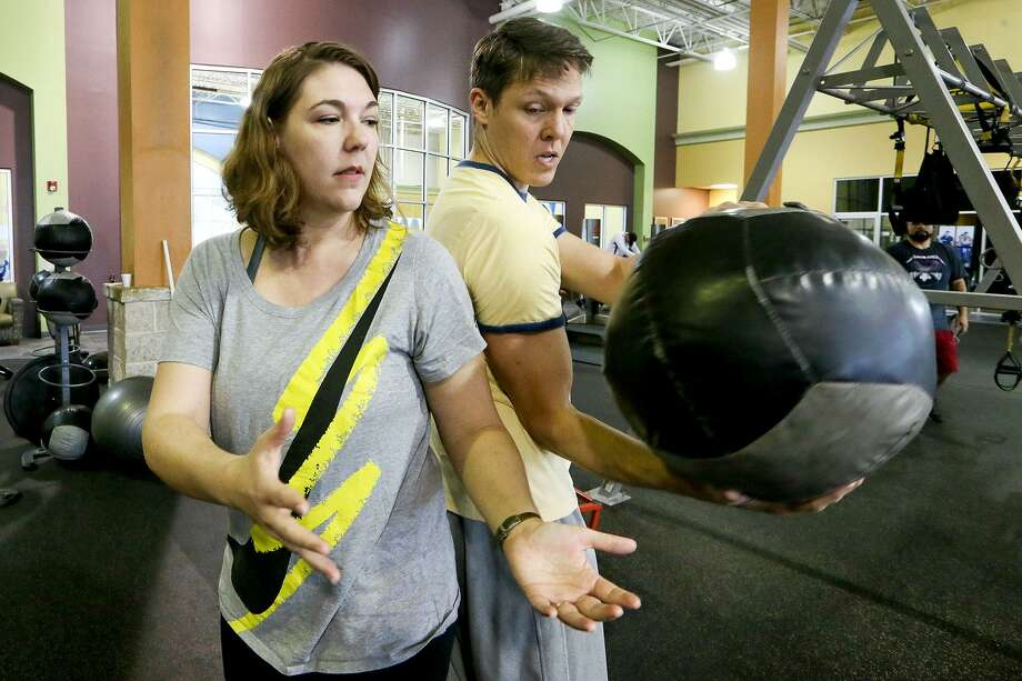 Don and Cindy McGeary, the nation's foremost researchers on the way chronic pain and personal relationships affect each other, do a medicine ball twist while working out together at Gold's Gym, 11761 Bandera Rd., on Sunday, March 5, 2017.  MARVIN PFEIFFER/ mpfeiffer@express-news.net Photo: Marvin Pfeiffer, Staff / San Antonio Express-News / Express-News 2017