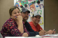 From left, Monica and Juan Gonzalez and Miguel Torres react as instructor Fernando Ramirez mixes humor with the night's lesson during the free ESL classes he holds every Tuesday night at the Port Arthur Public Library. Photo taken Tuesday, March 14, 2017 Kim Brent/The Enterprise