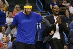 Golden State Warriors center JaVale McGee, left, and forward Kevin Durant, right, celebrate on the bench following a basket by the Warriors during the first quarter of an NBA basketball game against the Oklahoma City Thunder in Oklahoma City, Monday, March 20, 2017. (AP Photo/Sue Ogrocki)