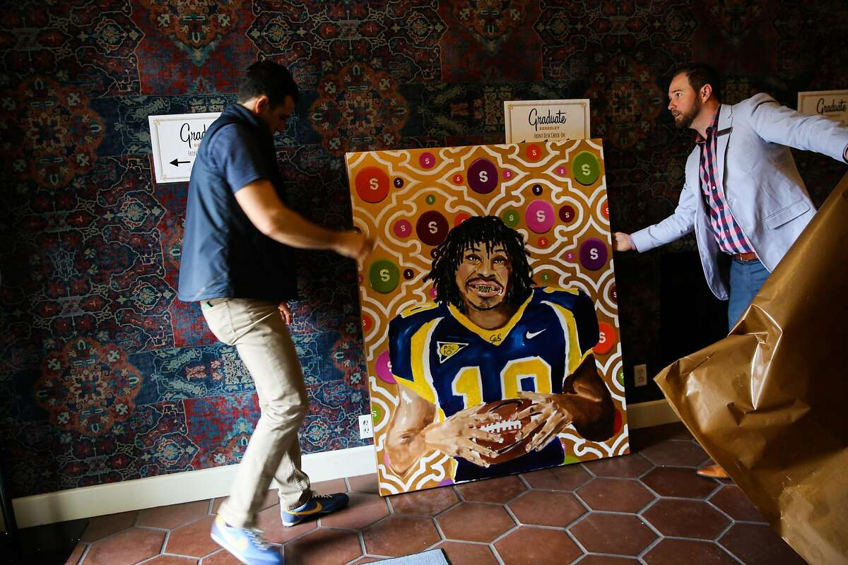 CEO of Graduate Hotels Ben Weprin (left) and Dell Dellinger (right) show off a piece of custom made art that was created for the new Hotel Durant, which has been renovated by Graduate Hotels in Berkeley, California, on Monday, March 20, 2017.