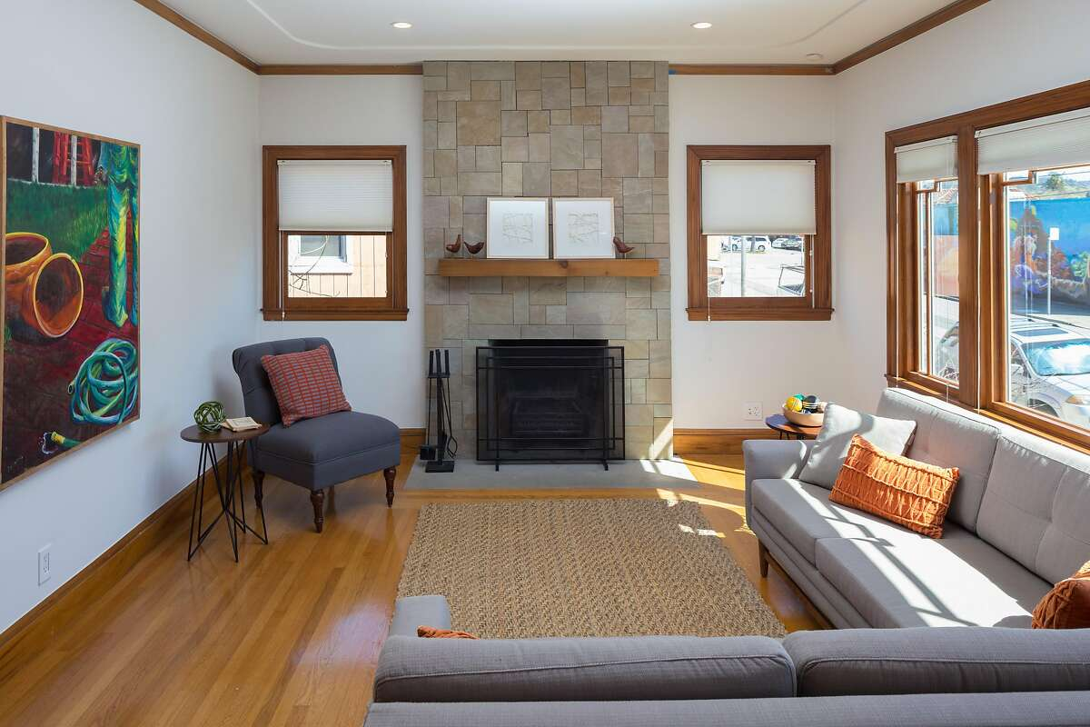 Sandstone slab tiles fashion a floor-to-ceiling surround for the living room's fireplace.�