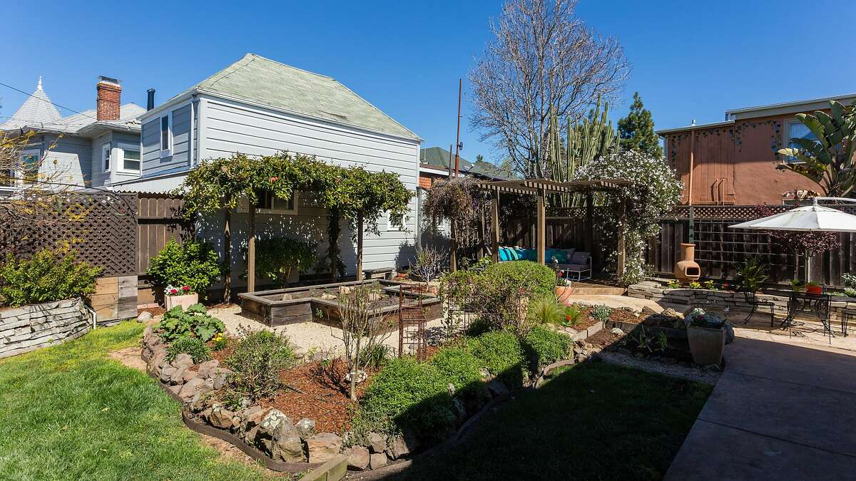 The wraparound backyard offers mature planting and raised garden beds.�