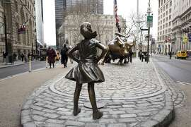 """In this March 8, 2017, the """"Fearless Girl"""" statue faces Wall Street's charging bull statue in New York. It took months of intricate planning by two corporate giants to install the statue under the veil of darkness in time for Wednesday's International Women's Day. The one-week permit for the installation downtown was extended by New York Mayor Bill de Blasio through April 2 and popular support for the piece to be kept permanently is growing, with petitions being signed. (AP Photo/Mark Lennihan)"""