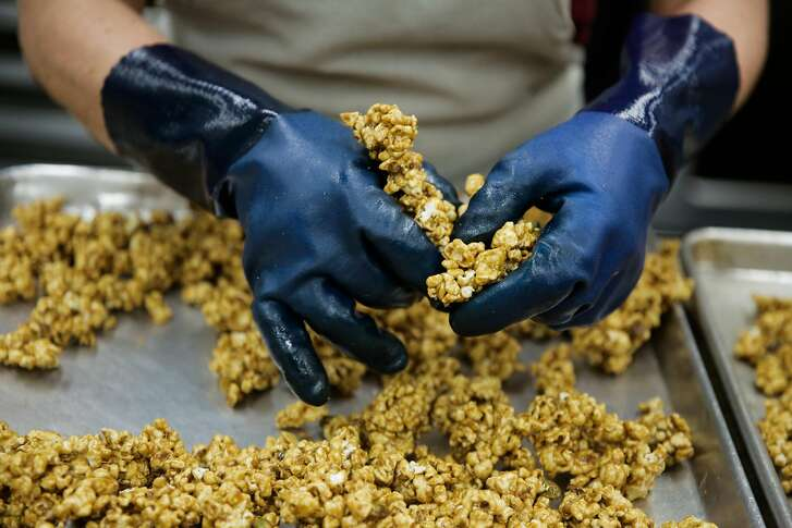 Carmen Sanchez breaks apart popcorn while making pistachio caramel popcorn at caramel company CC Made's production facility in Berkeley, California, on Monday, March 20, 2017.